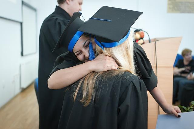 Dos graduadas se abrazan
